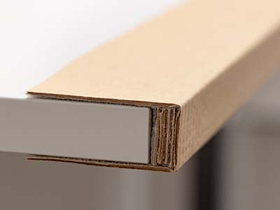 Beitragsbild zu Kantenschutz und Eckschutz. Abgebildet ist ein Kantenschutzprofil aus Wellpappe mit mehrlagigem Polster aus Wellpappe.
